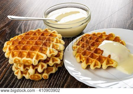 Teaspoon In Transparent Bowl With Condensed Milk, Stack Of Waffles, White Plate With Biscuit Waffle