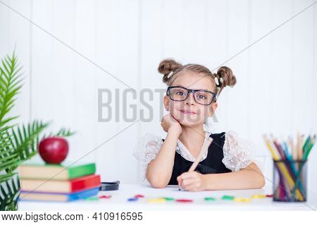 Happy Smiling Pupil At The Desk. Girl In The Class Room With Pencils, Books. Kid Girl From Primary S