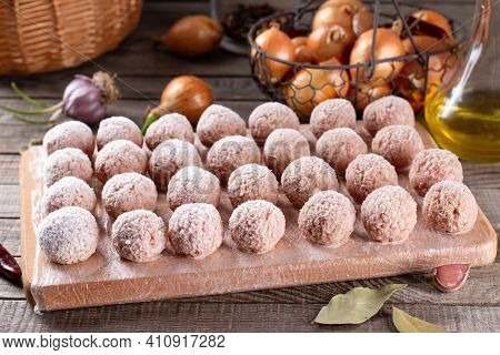Frozen Meatballs Lie On A Wooden Board. Raw Meat Semi-finished Products Are Ready For Cooking