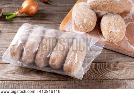 Plastic Bags With Frozen Meat And Cutlets In Plastic Bag On A Wooden Table