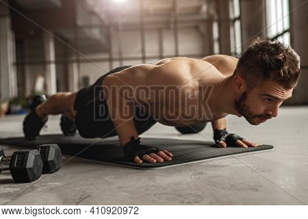 Muscular Man Doing Push Up Exercise On Mat Near Dumbbells During Intense Fitness Workout In Grungy G