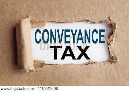 Conveyance Tax. Text On White Paper Over Torn Paper Background.