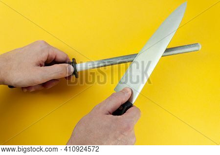Man Hand Sharpenes Knife On Yellow Background. Knife Sharpening Using A Knife Grinder.
