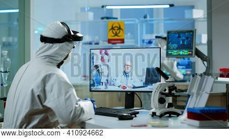 Chemist In Ppe Suit Listening Professional Doctor On Video Call, Discussing During Virtual Meeting I