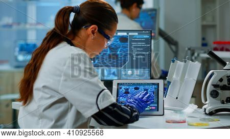 Scientist Using Digital Tablet Working In Modern Medical Research Laboratory, Analyzing Dna Informat