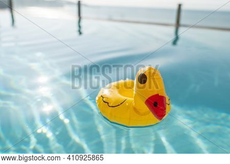 Cute Yellow Rubber Duck Floating On Blue Water In A Pool.