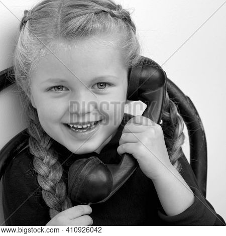 Smiling Girl Talking By Old Phone. Black And White Shot Of Lovely Kid Sitting On Chair In Vintage Ro
