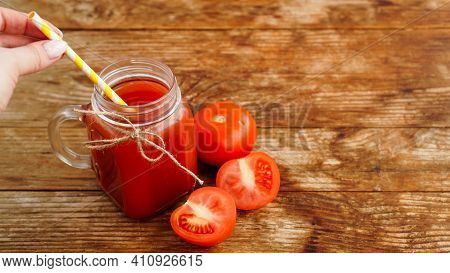 Female Hand Adding Paper Straw To Glass Of Tomato Juice On Wooden Table. Fresh Tomato Juice And Chop