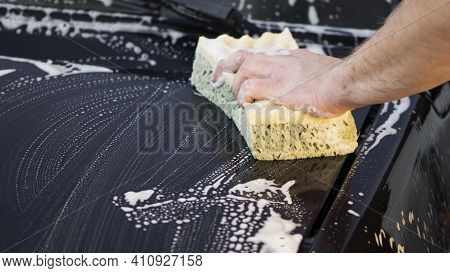 A Hand With A Washcloth And Soap Suds Washes The Hood Of The Car. Man Washing Car Hood With Washclot