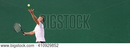 Tennis serve during match. Man tennis player playing throwing ball in the air serving playing on hard indoor court panoramic banner.
