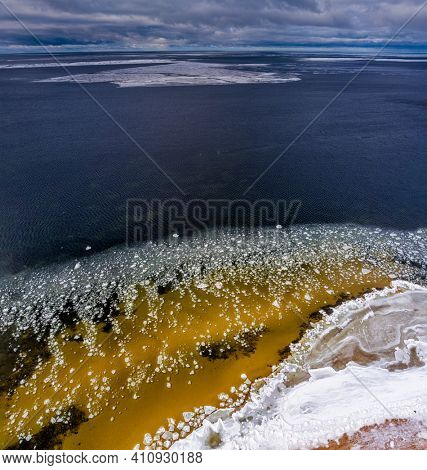 Ice blocks drifting around in a calm sea water creating interesting aerial patterns. Shot from drone