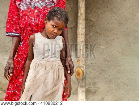 small african girl together with het grandmother in the village, in the yard .