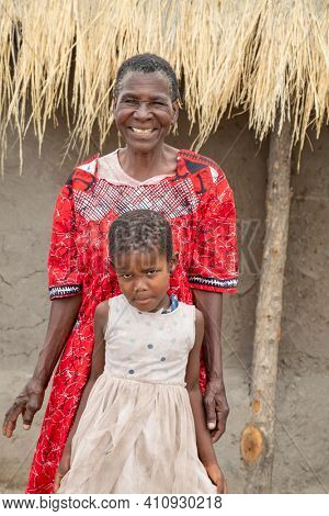 old African woman and her granddaughter standing in her yard in a village in Botswana