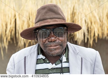 old african with sunglass standing in the yard in a village in botswana