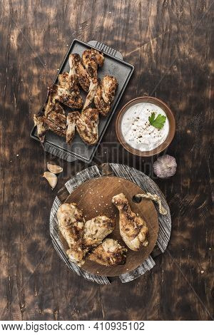 Grilled Chicken Wings And Drumsticks On A Wooden Board And A Flat Black Plate With White Sauce On A