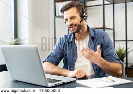 Confident Man With Handsome Stubble, Wearing Headset, Talking In Front Of Computer, Wearing Casual C