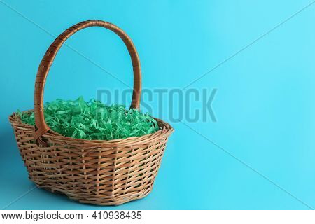 Easter Basket With Green Paper Filler On Light Blue Background, Space For Text