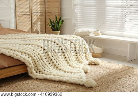 Knitted Merino Wool Plaid On Bed Indoors. Interior Design