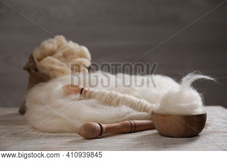 Soft White Wool And Spindles On Wooden Table. Space For Text