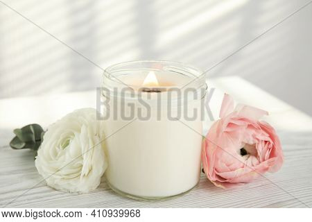 Candle With Burning Wooden Wick And Flowers On White Table