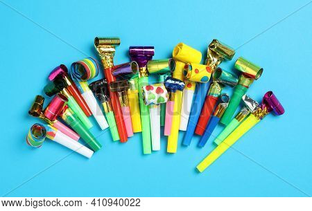 Colorful Party Blowers On Light Blue Background, Flat Lay
