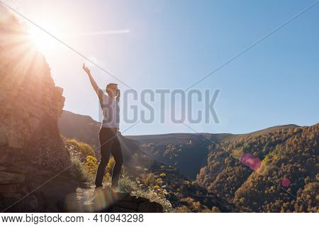 Muscular Guy Silhouette Stands On Rocky Cliff Edge At Large Stone Against Green Forestry Mountains A