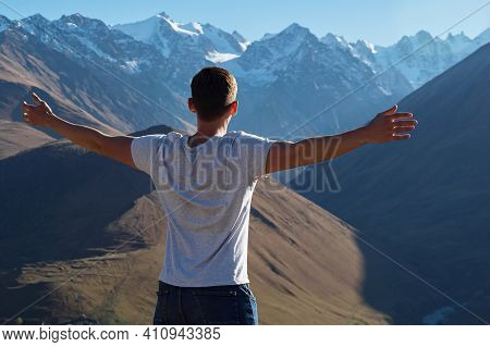 Athletic Guy In White T-shirt Stands On Hilltop And Looks At Large Mountains Peaks Stretching Arms U