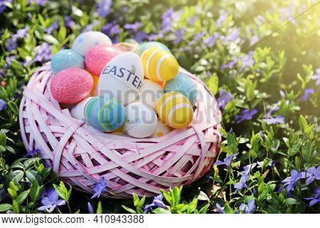 Easter Holiday.pink Wicker Nest With Easter Decorative Eggs In Purple Spring Flowers.easter Eggs In