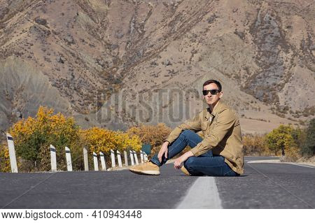 Man In Brown Shirt And Sunglasses Sits On Empty Grey Asphalt Road Surrounded By Yellow Orange Trees