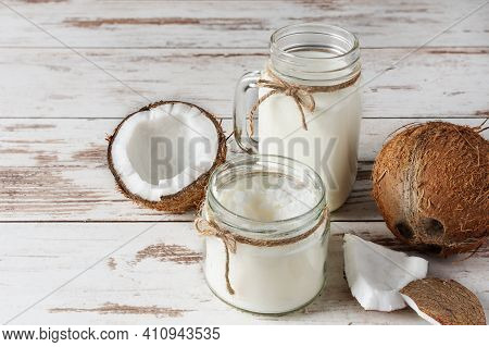 Jar Of Coconut Vegan Milk And Coconut Butter With Coconut Halves On White Wooden Table. Vegan Coconu