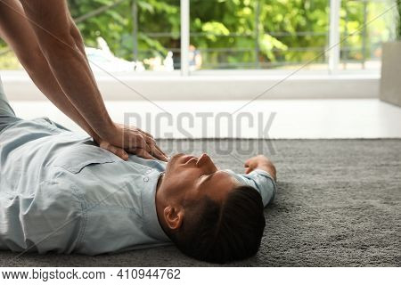 Passerby Performing Cpr On Unconscious Man Indoors. First Aid
