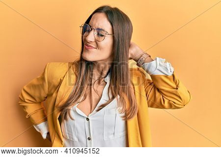 Young beautiful woman wearing business style and glasses suffering of neck ache injury, touching neck with hand, muscular pain