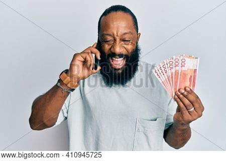 Young african american man having conversation talking on the smartphone holding norwegian krona banknotes smiling and laughing hard out loud because funny crazy joke.