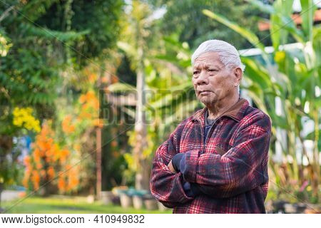 Portrait Of An Elderly Asian Man With Gray Hair, Arms Crossed And Looking Away While Standing In A G