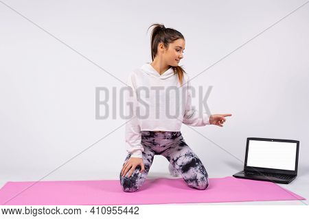 A Young Woman Is Doing Stretching And Choreography In Front Of A Laptop Screen On Yoga Mat, Online L