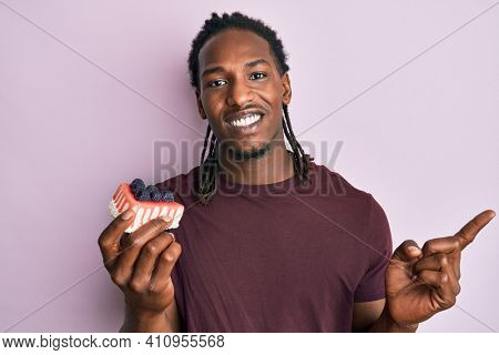 African american man with braids holding plate with cheesecake smiling happy pointing with hand and finger to the side