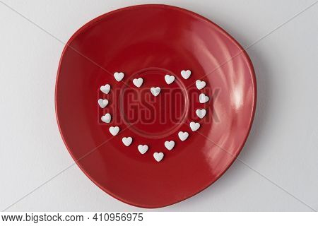 The White Pills Are Arranged In The Shape Of A Heart On A Red Plate