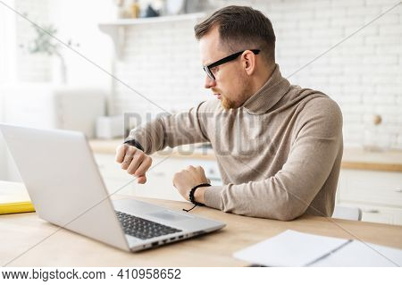 Busy Young Bearded Entrepreneur Or Teacher In Glasses Sitting At Home And Working On Laptop, Checkin