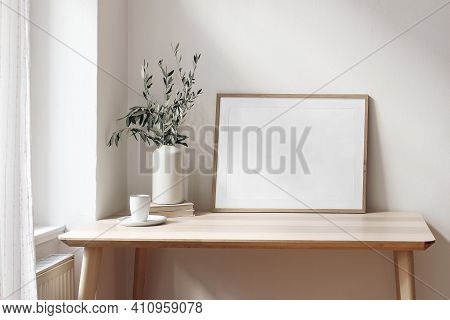 Home Office Concept. Empty Horizontal Wooden Picture Frame Mockup. Cup Of Coffee On Wooden Table. Wh