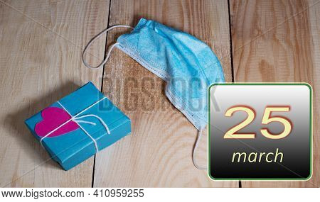 March 25, 25th Day Of Month. Medical Mask From Covid 19 And Box With Gift Lie On Wooden Boards. Spri