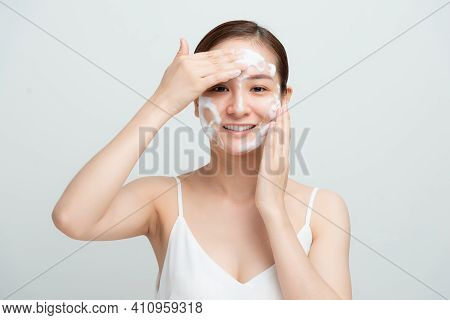 Smiling Beautiful Asian Girl Using Foaming Cleanser. Face Washing Concept Isolated On White Backgrou