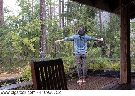 Woman Spread Her Arms To The Sides And Enjoys The Warm Rain, Standing On The Veranda And Looking At