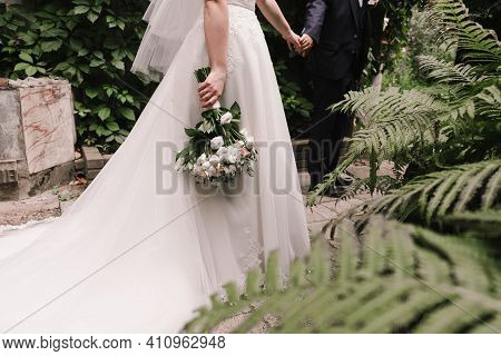 The Bride And Groom Hold Hands. Stylish Groom And Bride. .