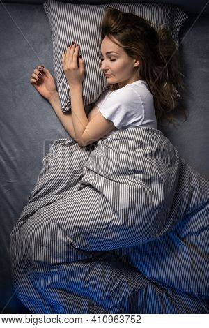 Pretty, young woman sleeping in her bed late in the morning on a weekend - compensating for the lack of sleep