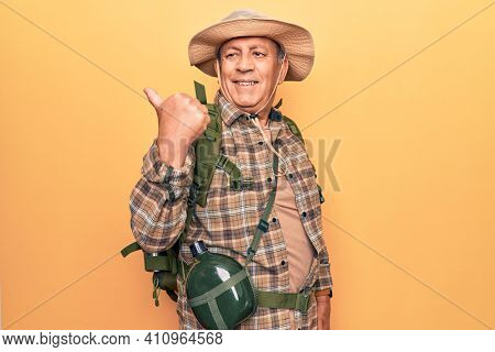 Senior man with grey hair wearing hiker backpack and water canteen pointing thumb up to the side smiling happy with open mouth