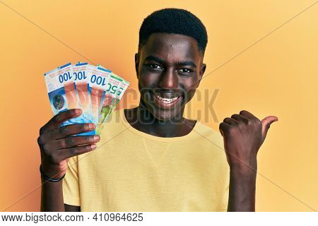Young african american man holding swiss franc banknotes pointing thumb up to the side smiling happy with open mouth