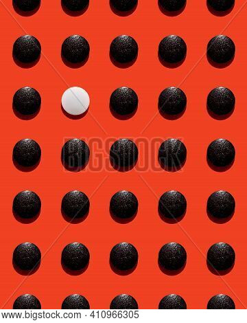 One White Disk Among Black Disks Pattern Isolated On Red As A Background