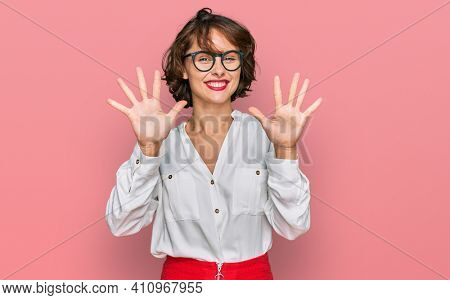 Young hispanic woman wearing business style and glasses showing and pointing up with fingers number ten while smiling confident and happy.