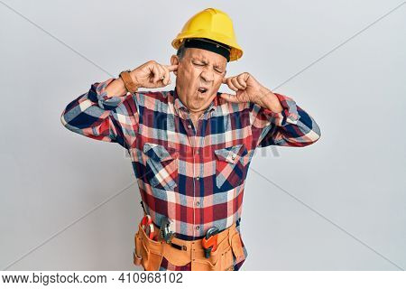 Senior hispanic man wearing handyman uniform covering ears with fingers with annoyed expression for the noise of loud music. deaf concept.