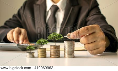 A Businessman Holding A Coin With A Tree That Grows And A Tree That Grows On A Pile Of Money. The Id